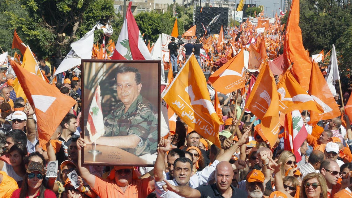 Supporters of the Free Patriotic Movement (FPM) carry flags and a picture of Christian politician and FPM founder Michel Aoun during a rally to show support for him and to mark the October 13 anniversary, near the presidential palace in Baabda, near Beirut, Lebanon October 11, 2015. Thousands of Lebanese rallied near the presidential palace on Sunday in a show of support for Christian politician Michel Aoun, pressing their demand for him to fill the vacant presidency. The rally was called to mark events in October 1990, near the end of the Lebanese civil war, when the Syrian army captured Baabda. Aoun - head of one of two rival administrations at the time - was forced out of the presidential palace and later into exile. REUTERS/Mohamed Azakir