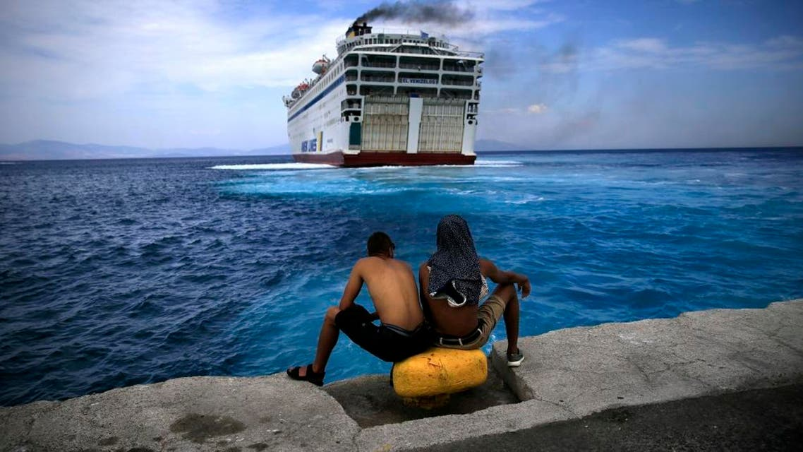 """Two Syrian refugees sit at the dock of the port of Kos as the passenger ship """"Eleftherios Venizelos"""" backs into the quay on the Greek island of Kos, August 14, 2015. (Reuters)"""
