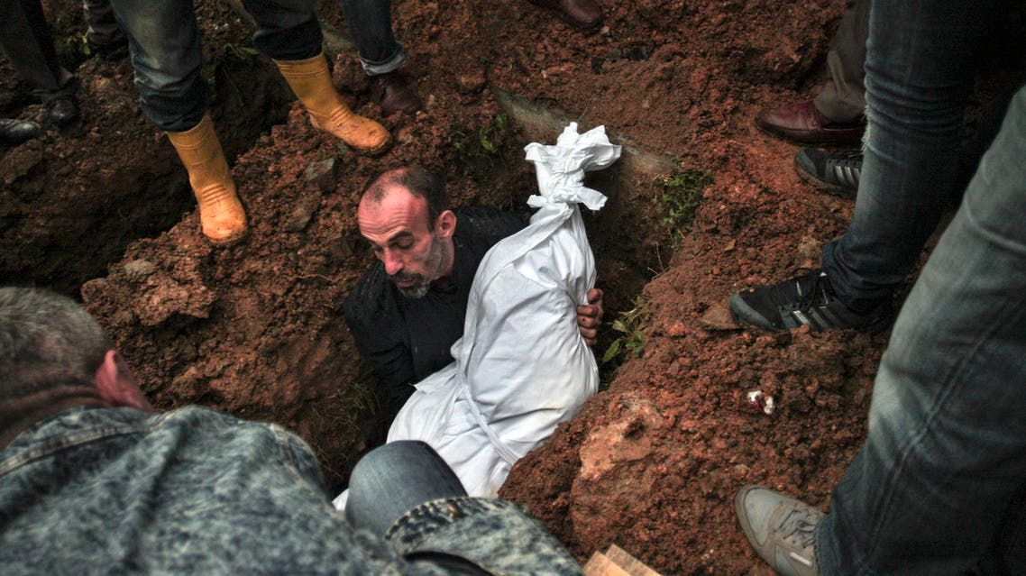 A man lowers the body of Sarigul Tuylu, 35, a mother of two that was killed in Saturday's bombing attacks in Ankara, Turkey, during her funeral in Istanbul, Sunday, Oct. 11, 2015. (Reuters)