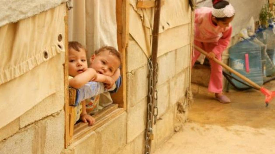 Syrian refugee children look on from a window during a sandstorm at a refugee camp on September 8, 2015 near the Bekaa Valley village of Taalabaya Lebanon