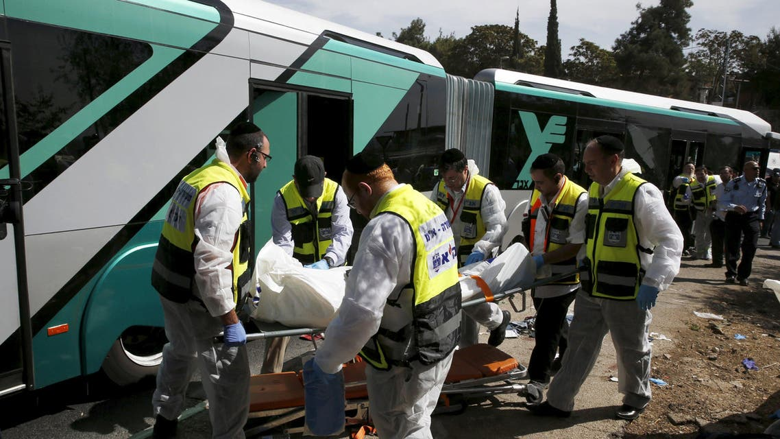 Members of Zaka Rescue and Recovery team carry a covered body from scene of an attack on a Jerusalem bus