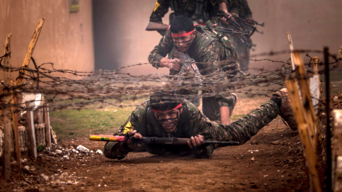 Fighters of the Kurdish People's Protection Units (YPG) crawl under barbed wires with their weapons at a military training camp in Ras al-Ain February 13, 2015. Picture taken February 13, 2015. (Reuters)