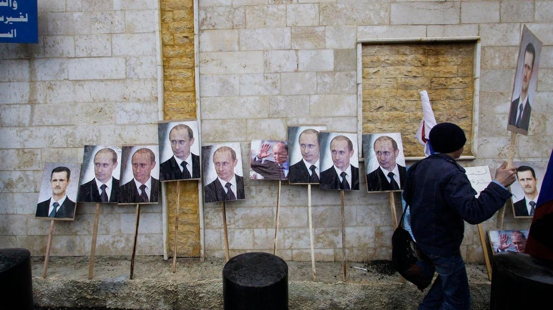 photos of Syrian President Bashar Assad and Russian President Vladimir Putin are propped against a wall during a pro-Syrian government protest in front of the Russian Embassy in Damascus. (File photo: AP)