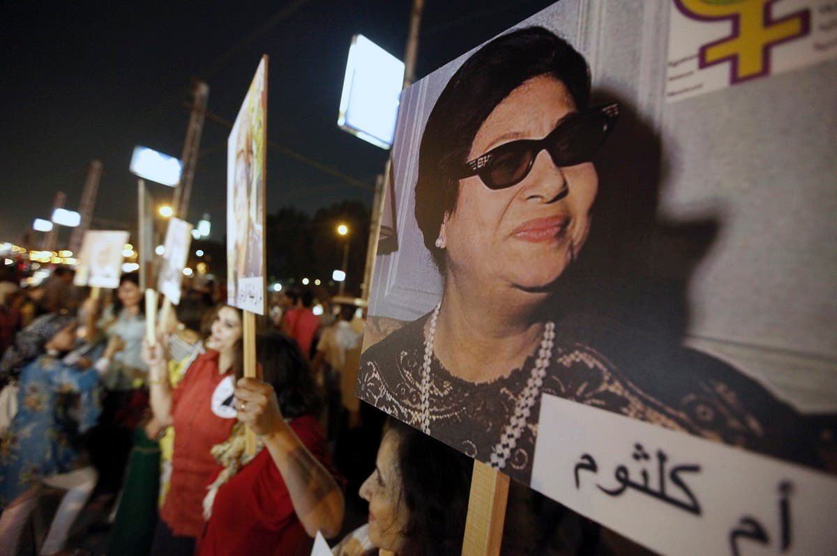 Women carry a picture of late Egyptian singer Umm Kalthoum during a protest supporting women's rights. (Reuters)