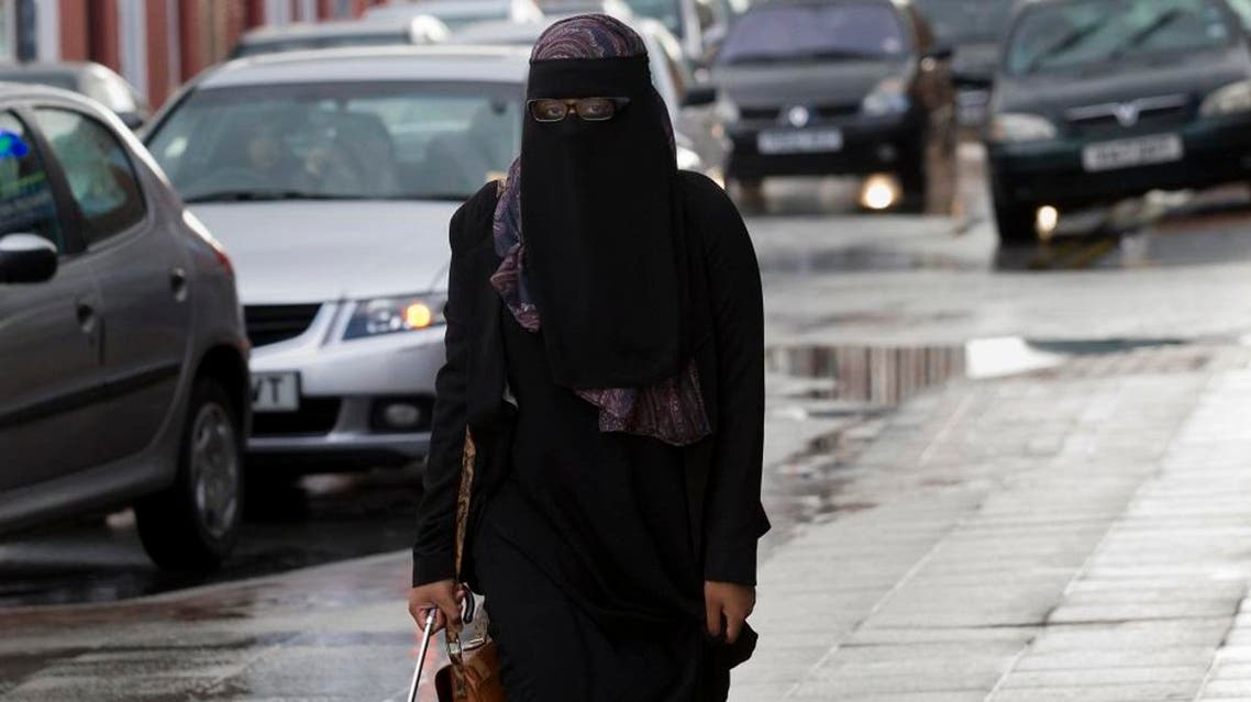 A member of the public wearing a full face veil is seen in Blackburn, England, Wednesday, Sept. 19, 2013. A judge ruled earlier this week that a female Muslim defendant may stand trial wearing a face-covering veil — but must remove it when giving evidence. The compromise ruling had some insisting it backs a woman's religious right to wear the veil, and others saying it shows British justice remains independent and won't bow to religious demands. (AP Photo/Jon Super)
