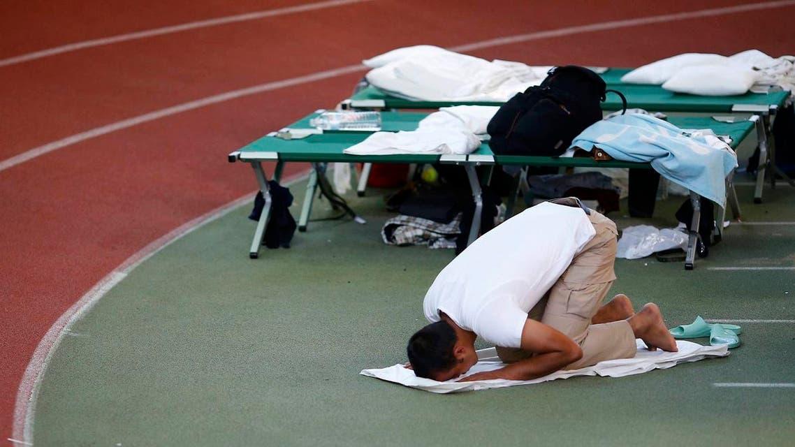 A Muslim asylum seeker prays at an temporary shelter in a sports hall in Hanau, Germany. (AP)
