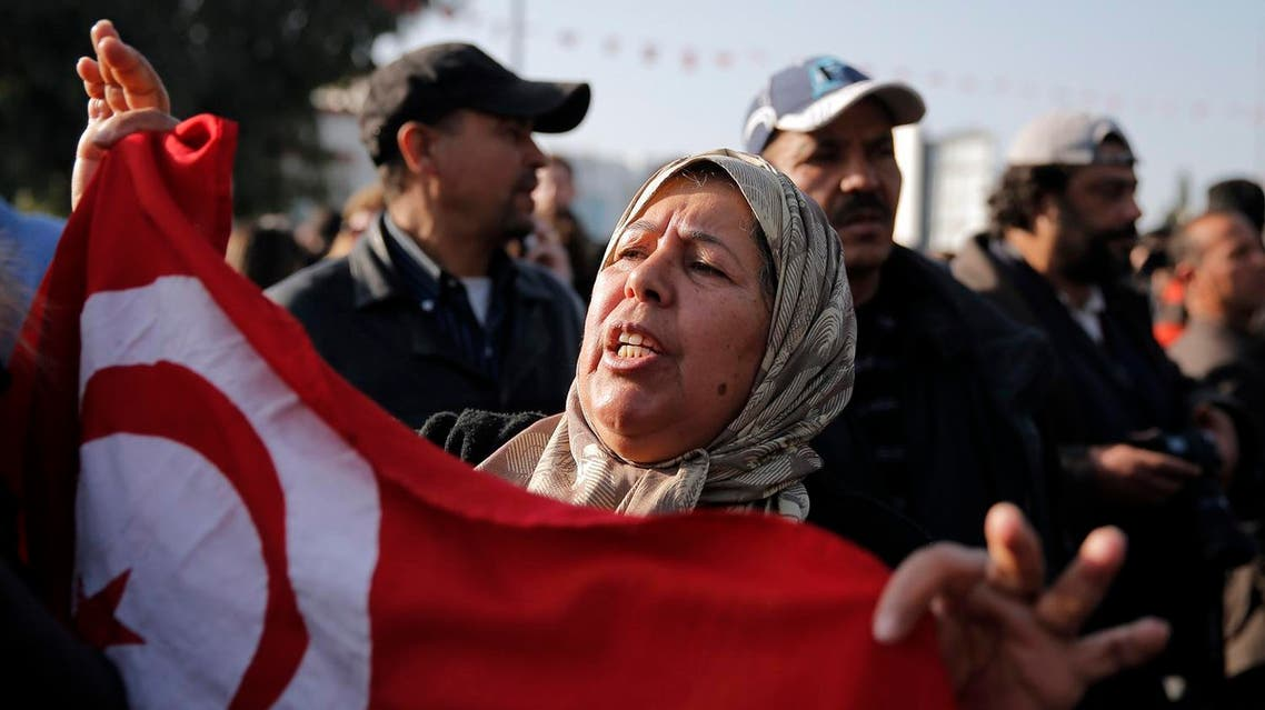 A woman holds a Tunisian national flag as she demonstrates in front of the National Bardo Museum. (AP)