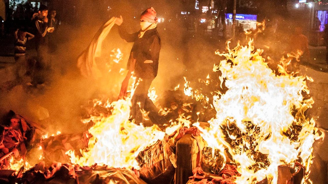 Leftist protesters stand by a barricade they set on fire, during minor clashes with Turkish security forces following a protest against Saturday's Ankara bombing attacks, in Istanbul's Gazi district on, Oct. 12.
