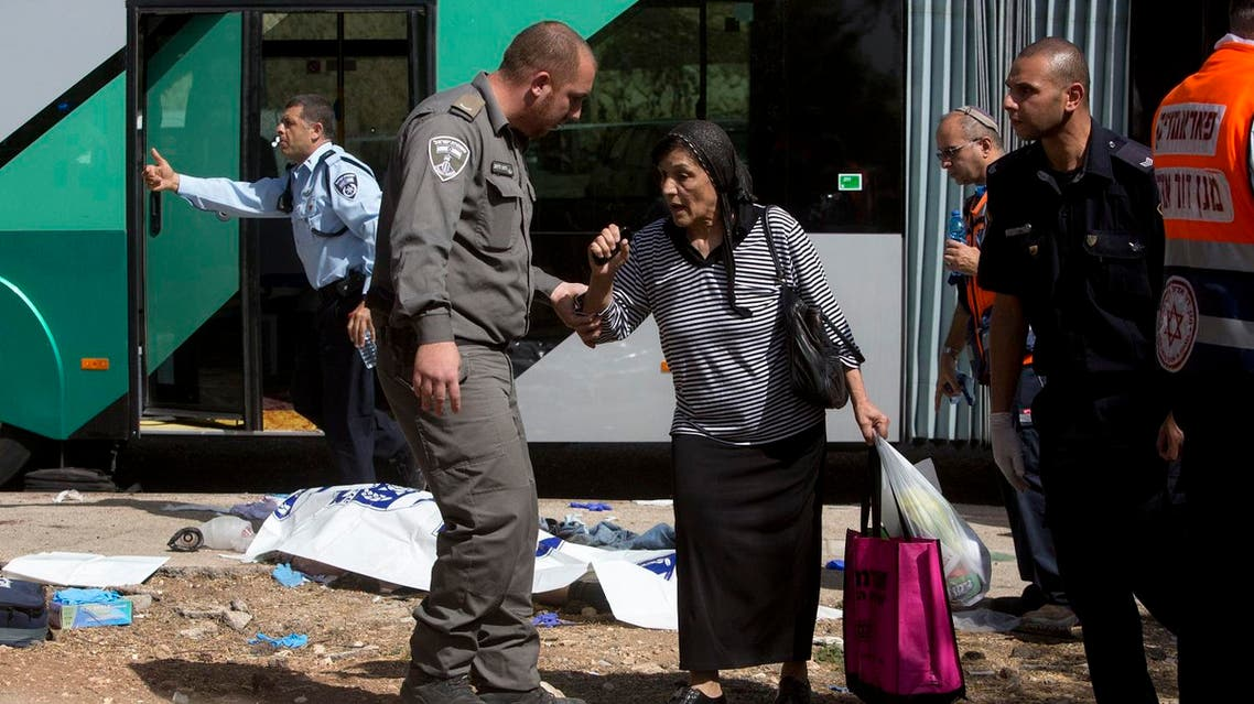 An Israeli border police officer escorts a woman at the scene of a shooting attack in Occupied Jerusalem. (File photo: AP)