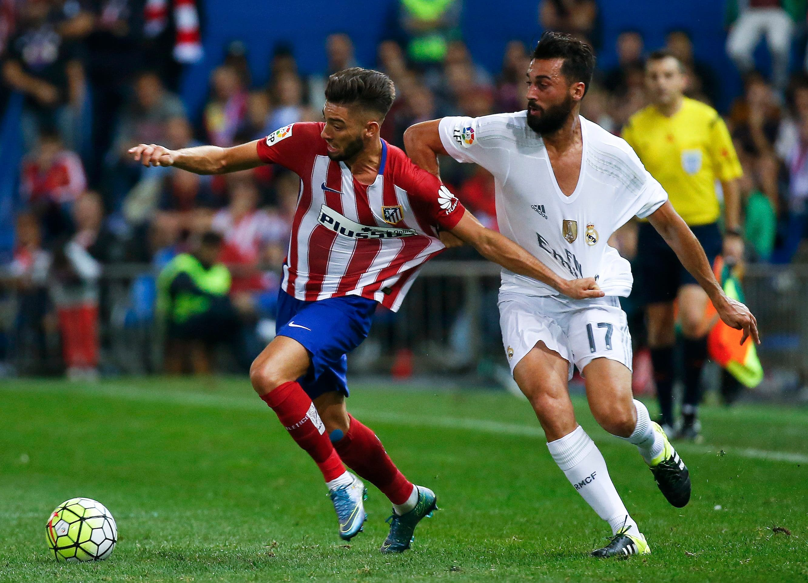 Atletico Madrid's Yannick Carrasco is challenged by Real Madrid's Alvaro Arbeloa during their Spanish first division derby soccer match in Madrid