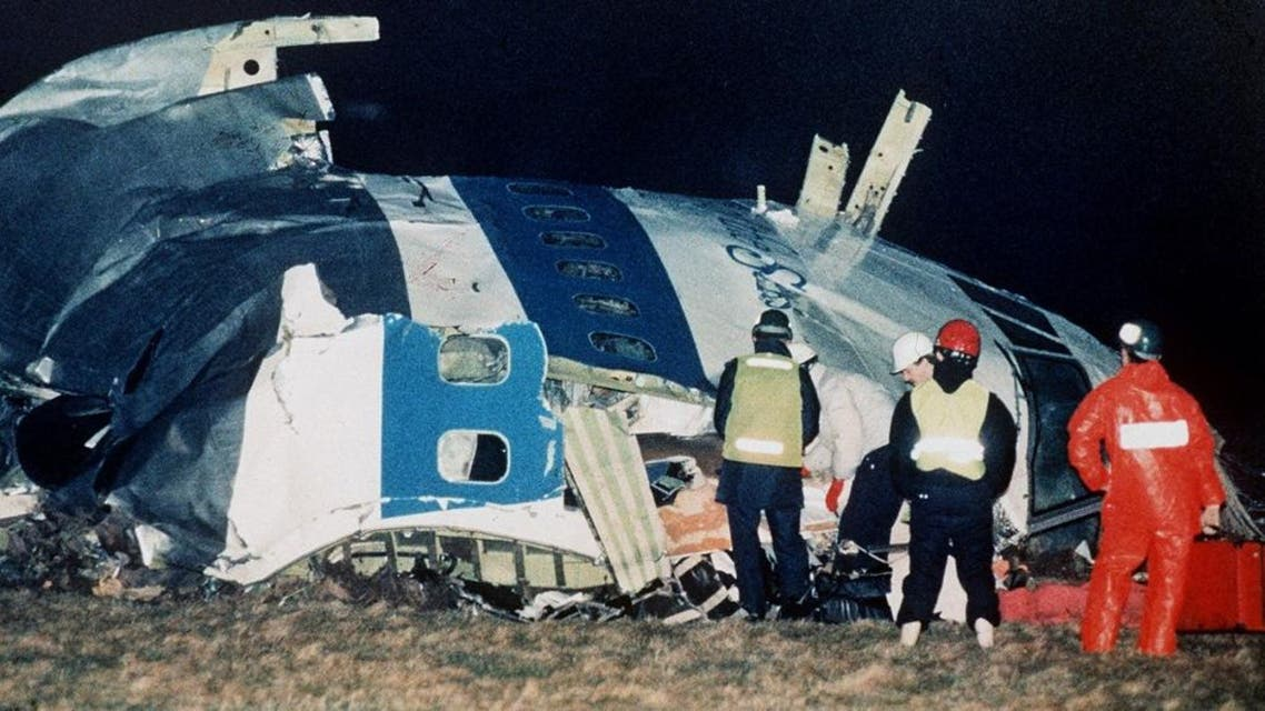 Rescue workers examine the nose of Pan Am Flight 103 near the town of Lockerbie, Scotland on Dec. 21, 1988. (File: AP)