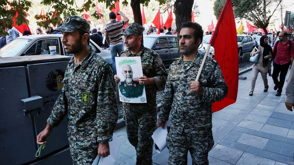 A member of the Iranian Revolutionary Guard holds a poster of Gen. Hossein Hamedani during his funeral ceremony in Tehran. (AP)