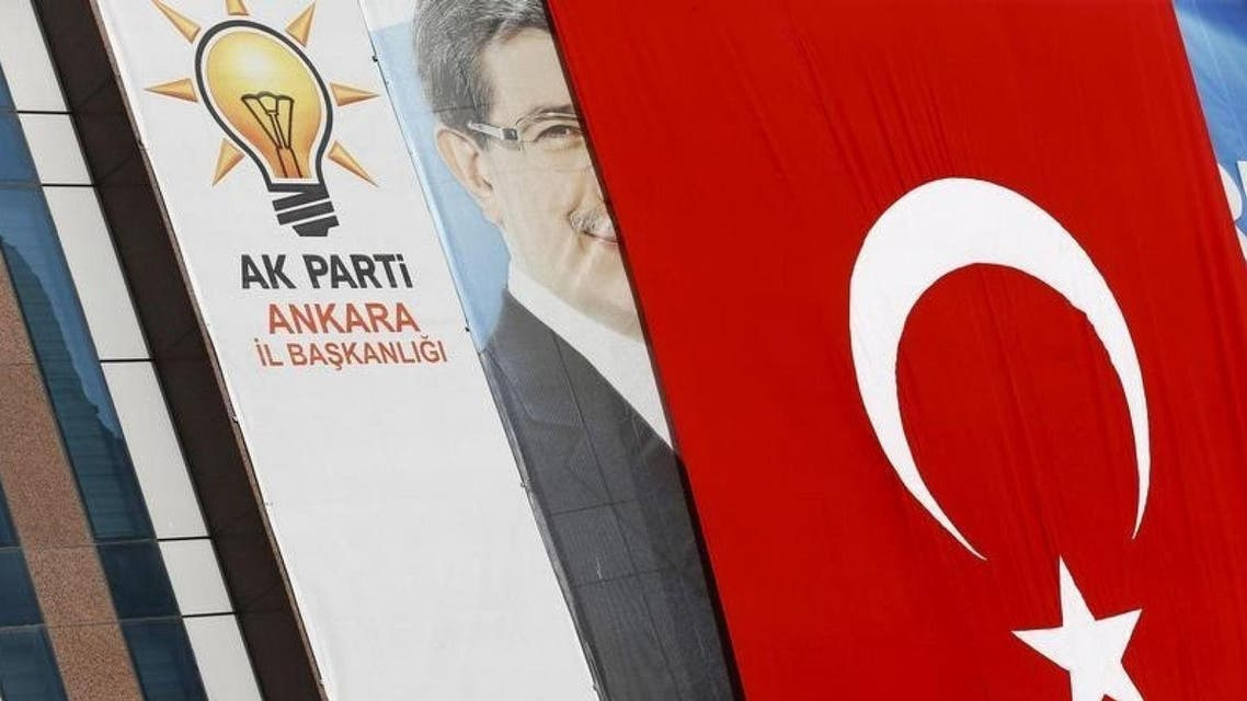 A big Turkish flag partly covers the portrait of Turkish Prime Minister Ahmet Davutoglu hung on an office of Turkey's ruling AK Party. (Reuters)