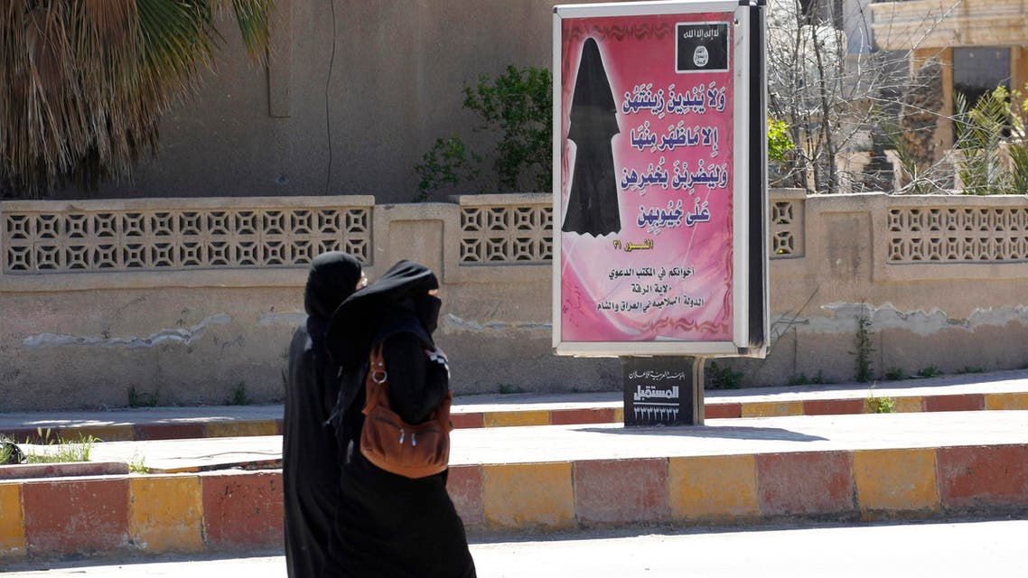 Veiled women walk past a billboard that carries a verse from Koran urging women to wear a hijab in the northern province of Raqqa. (File photo: Reuters)