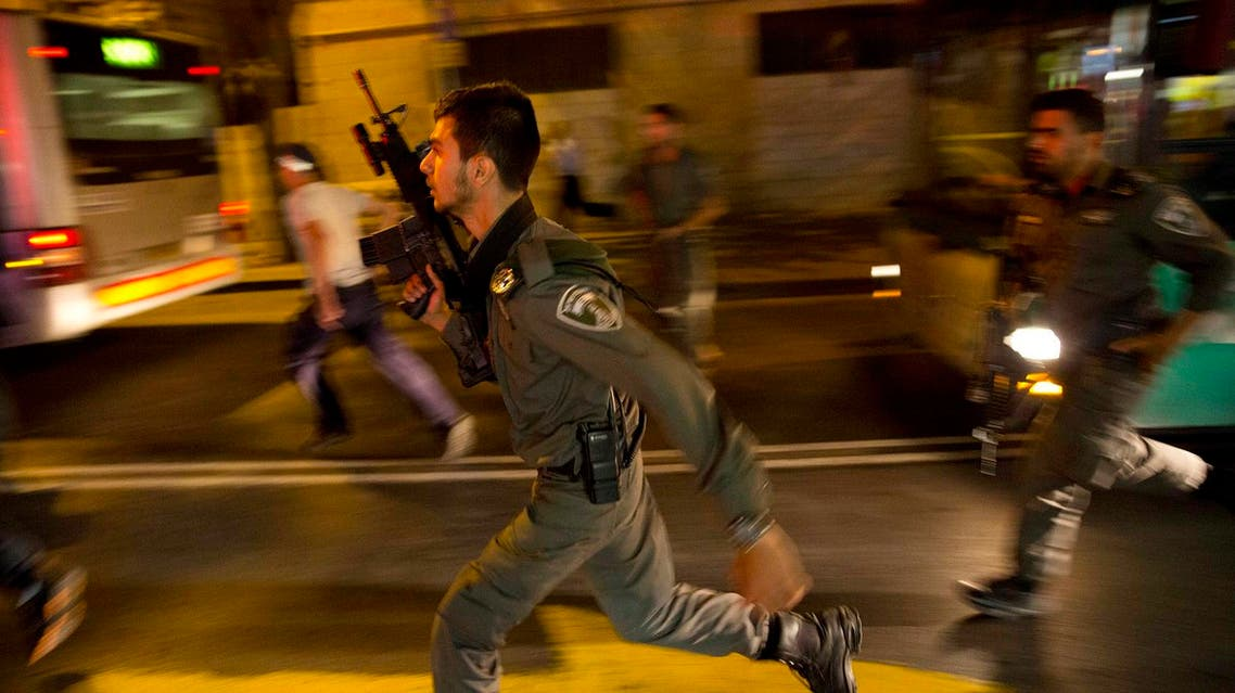Israeli policemen run looking for a possible stabbing suspect in Jerusalem. (AP)