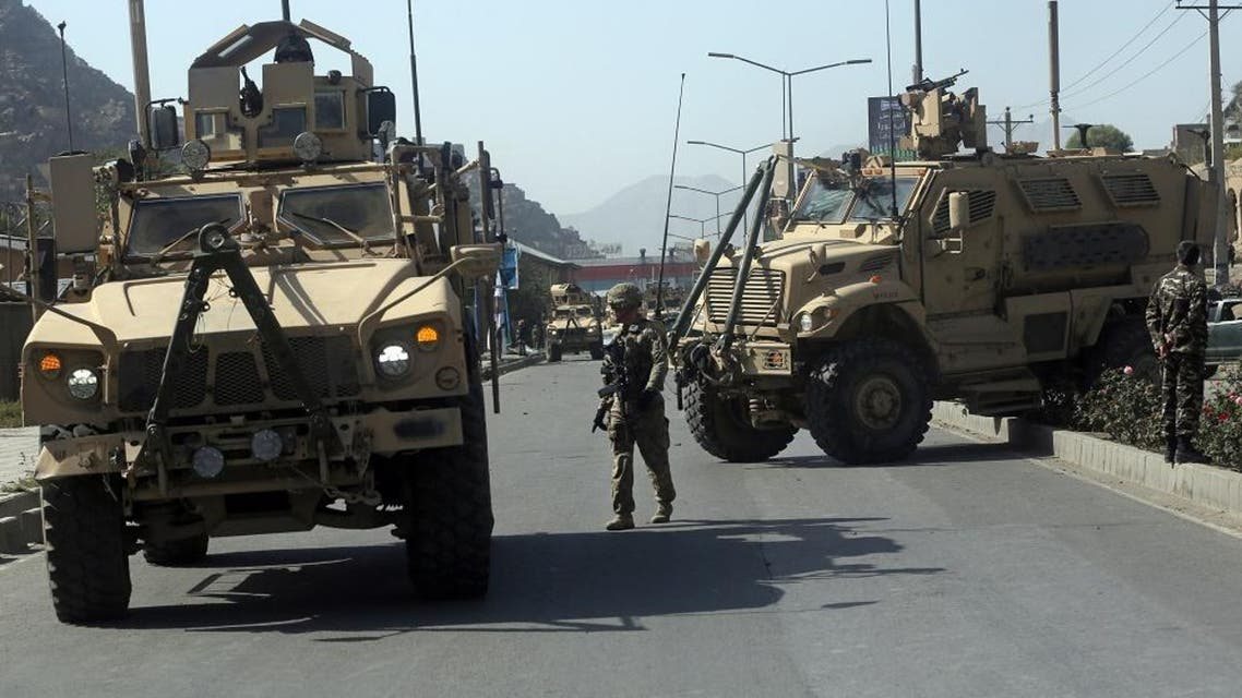 A U.S. soldier directs his colleague at the site a bomb attack that targeted several armored vehicles belonging to forces attached to the NATO Resolute Support Mission, in downtown of Kabul, Afghanistan, Sunday, Oct. 11, 2015. Gen. Abdul Rahman Rahimi, the Kabul city police chief, said that three Afghan civilians were wounded in the attack that damaged one of the vehicles but caused no fatalities. (AP Photo/Massoud Hossaini)