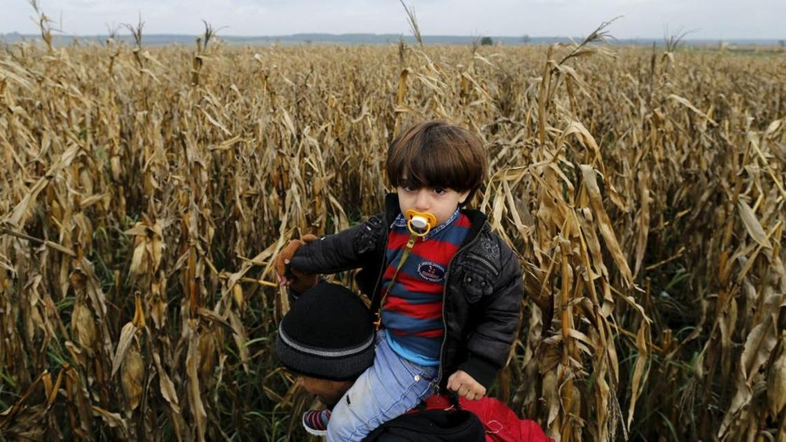 A migrant carries a child on his shoulders as he walks to cross the border into Croatia, near the town of Sid in Serbia. (File: Reuters)