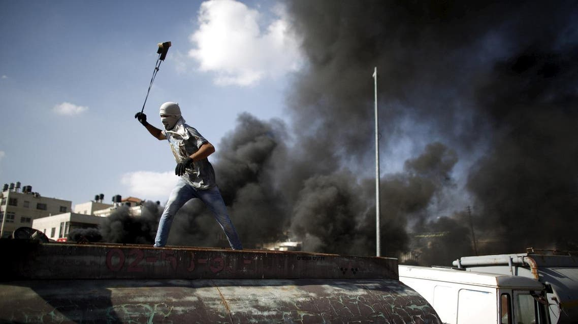 Palestinian protester uses a sling to hurl stones towards Israeli troops during clashes near the Jewish settlement of Beit El. (Reuters)
