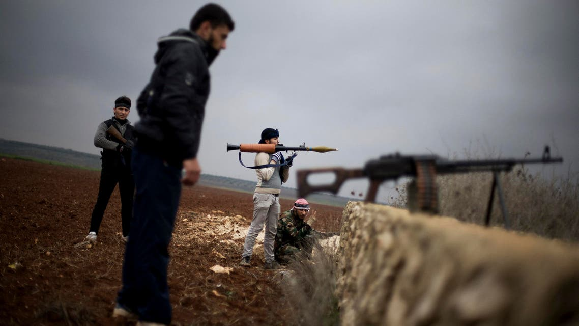 Free Syrian Army fighters take their positions, close to a military base, near Azaz, Syria.