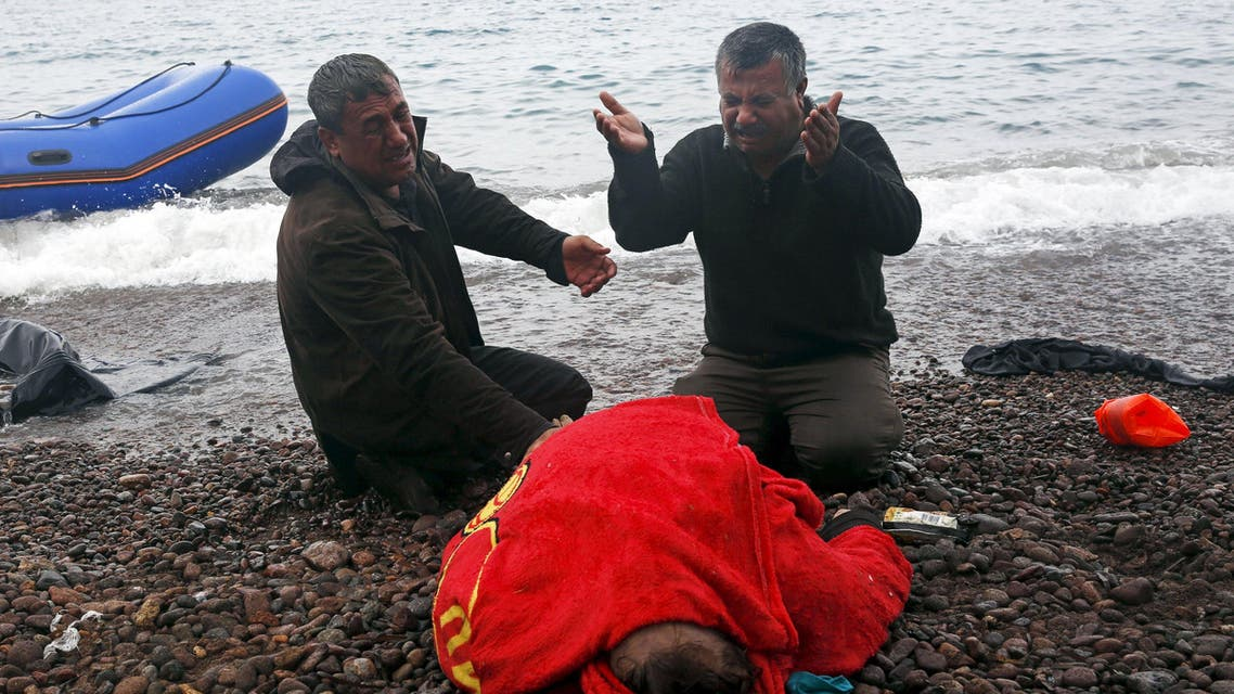 ATTENTION EDITORS - VISUAL COVERAGE OF SCENES OF INJURY OR DEATH The body of a 65-year old Iraqi refugee woman is covered with a towel as her husband (R) and a relative mourn, following their arrival on the Greek island of Lesbos in a dinghy, after crossing a part of the Aegean Sea from the Turkish coast, October 16, 2015. According to the relatives, the woman drowned while the members of the family were forced violently by smugglers to leave the Turkish coasts in a dinghy that filled immediately with sea water. REUTERS/Giorgos Moutafis