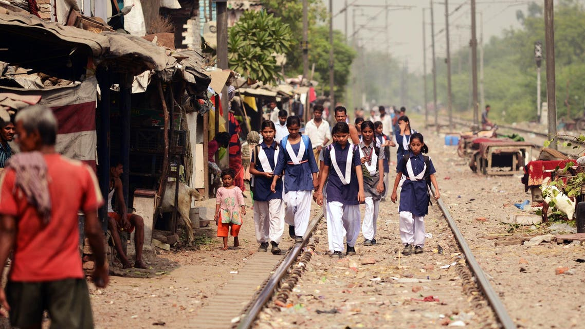 Indian girls walk on a railway track near a slum area of New Delhi on October 13, 2015 where a four-year-old girl was raped.