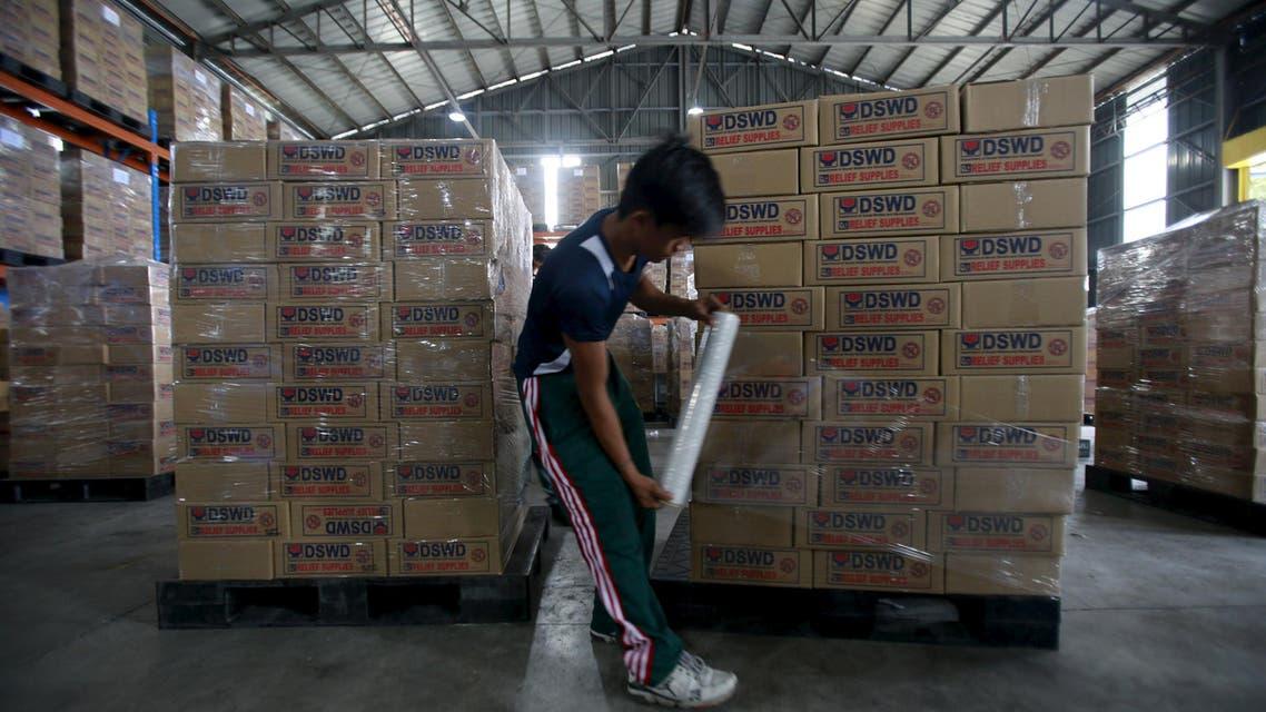 عامل يجهز المساعدات التي ستُرسل إلى المناطق التي سيضربها الإعصار كوبو في الفيليبين