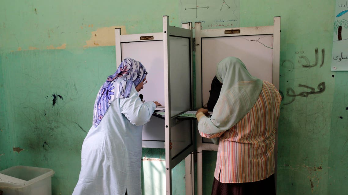 Egyptian voters cast their ballots at a polling station during the first round of parliamentary elections, in Giza, Cairo, Egypt, Sunday, Oct. 18, 2015. (AP Photo/Amr Nabil)