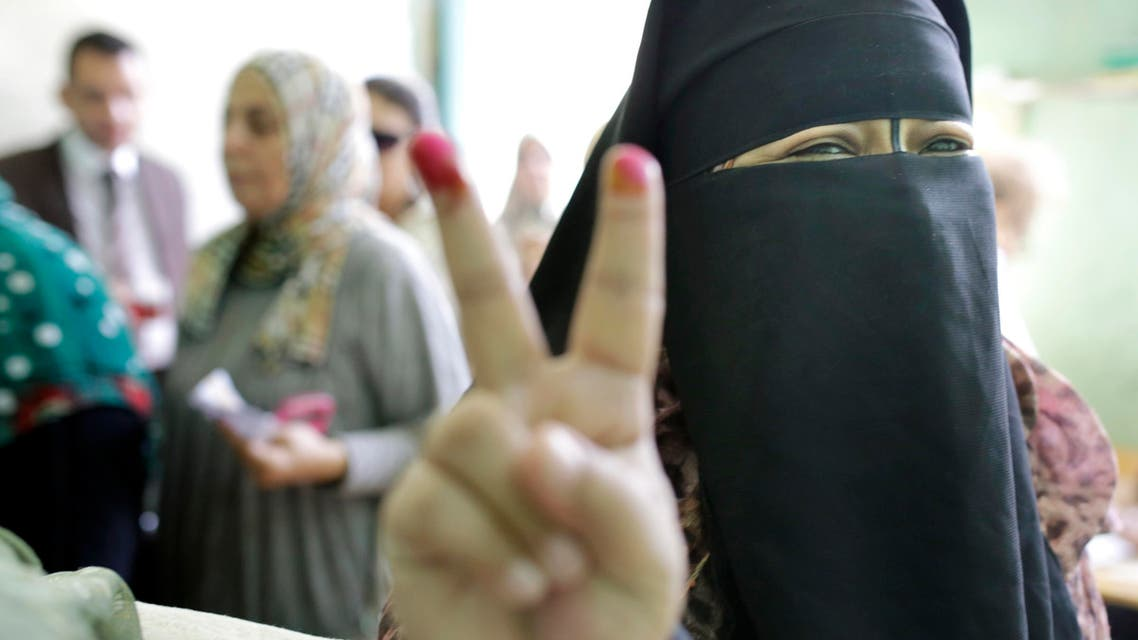 An Egyptian voter gestures with her inked fingers after casting her ballot at polling station during the first round of parliamentary elections, in Giza, Cairo, Egypt, Sunday, Oct. 18, 2015. (AP)