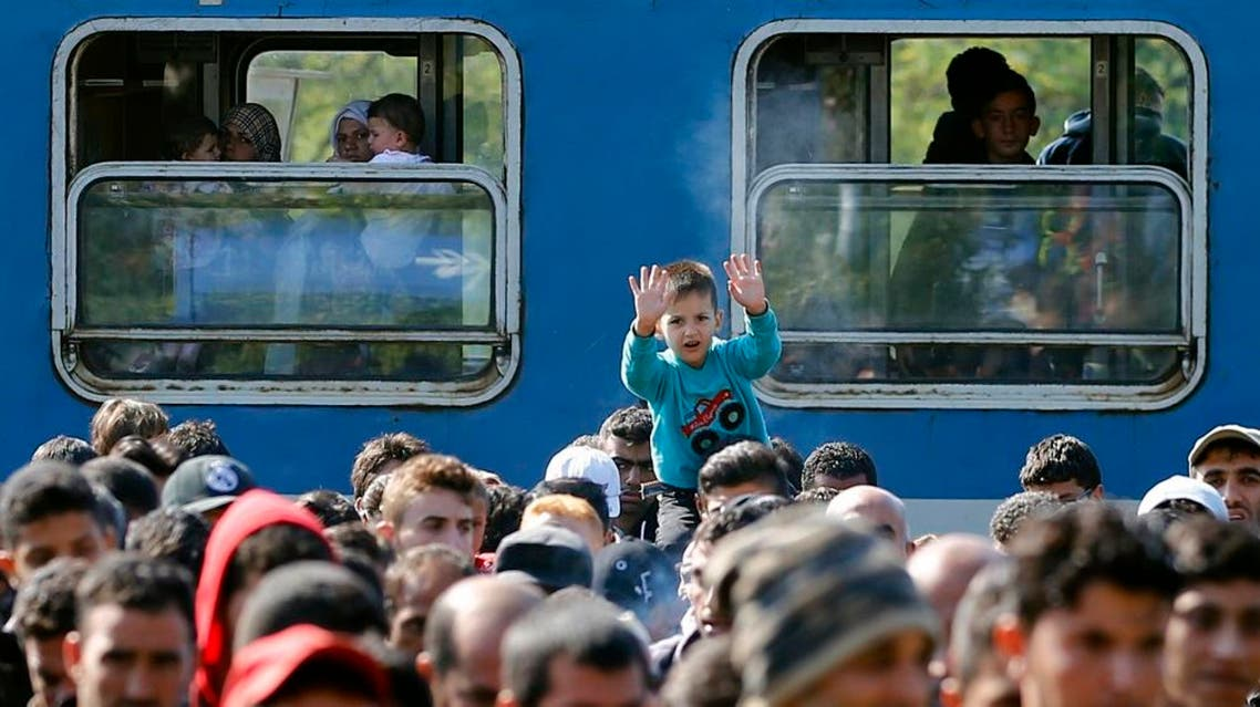 A boy reacts as migrants walk towards Austria from the train station in Hegyeshalom, Hungary , September 23, 2015. reuters