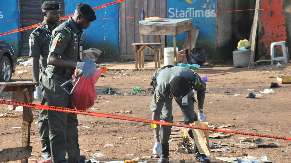 Police collect items at the site of a bomb explosion in Nyanya outskirt of Abuja, Nigeria, Saturday, Oct. 3, 2015. AP