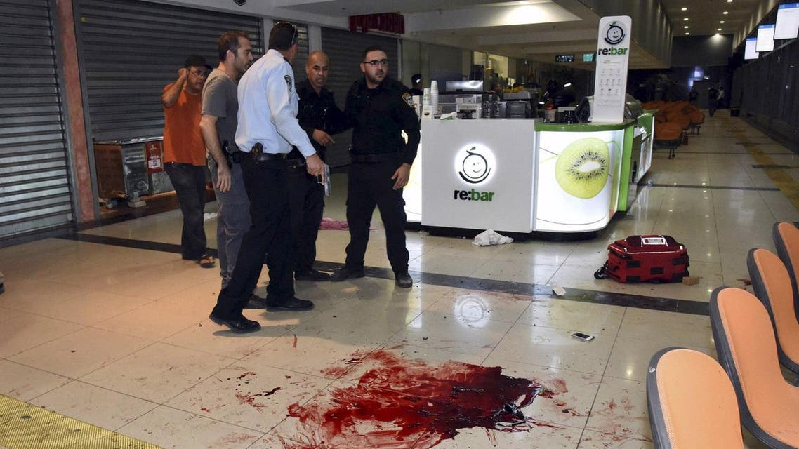 Israeli security personals stand next to blood on the floor at the Beersheba central bus station. (Reuters)