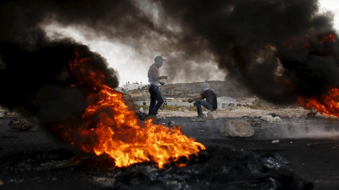 Smoke rises from burning tyres as Palestinian protesters are seen during clashes with Israeli troops near the Jewish settlement of Bet El, near the West Bank city of Ramallah. (Reuters)