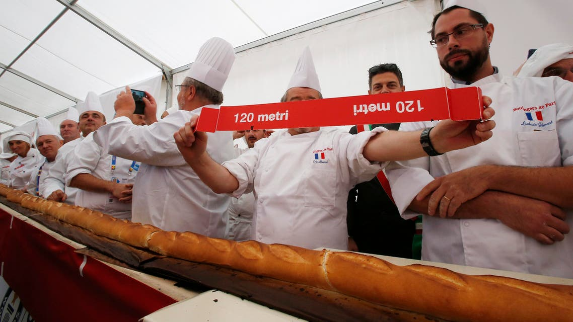 French and Italian bakers show a note reading 120 meters, at Expo 2015, in Rho, near Milan, Italy, Sunday, Oct. 18, 2015.