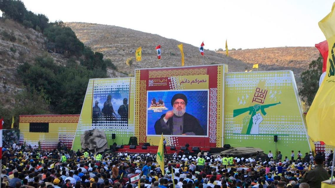 Hezbollah supporters listen to Hassan Nasrallah delivering a speech from a secret location through a giant TV screen. (File photo: AP)