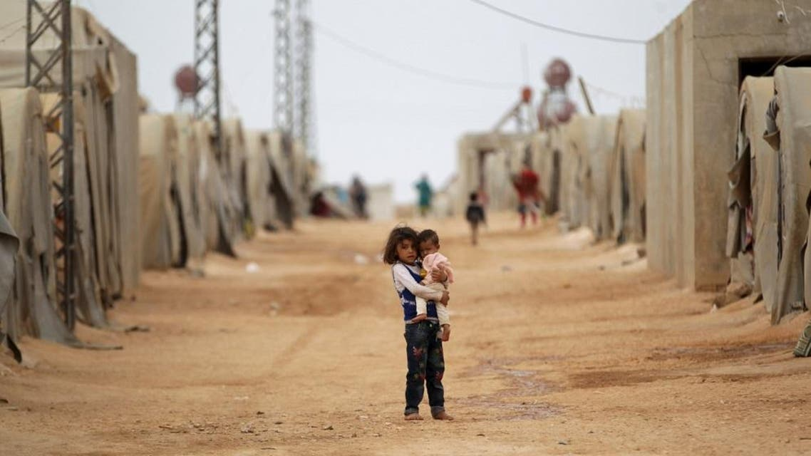 A girl carries a child inside a refugee camp for the internally displaced persons in Jrzinaz area, southern countryside of Idlib, Syria October 13, 2015. REUTERS/Khalil Ashawi