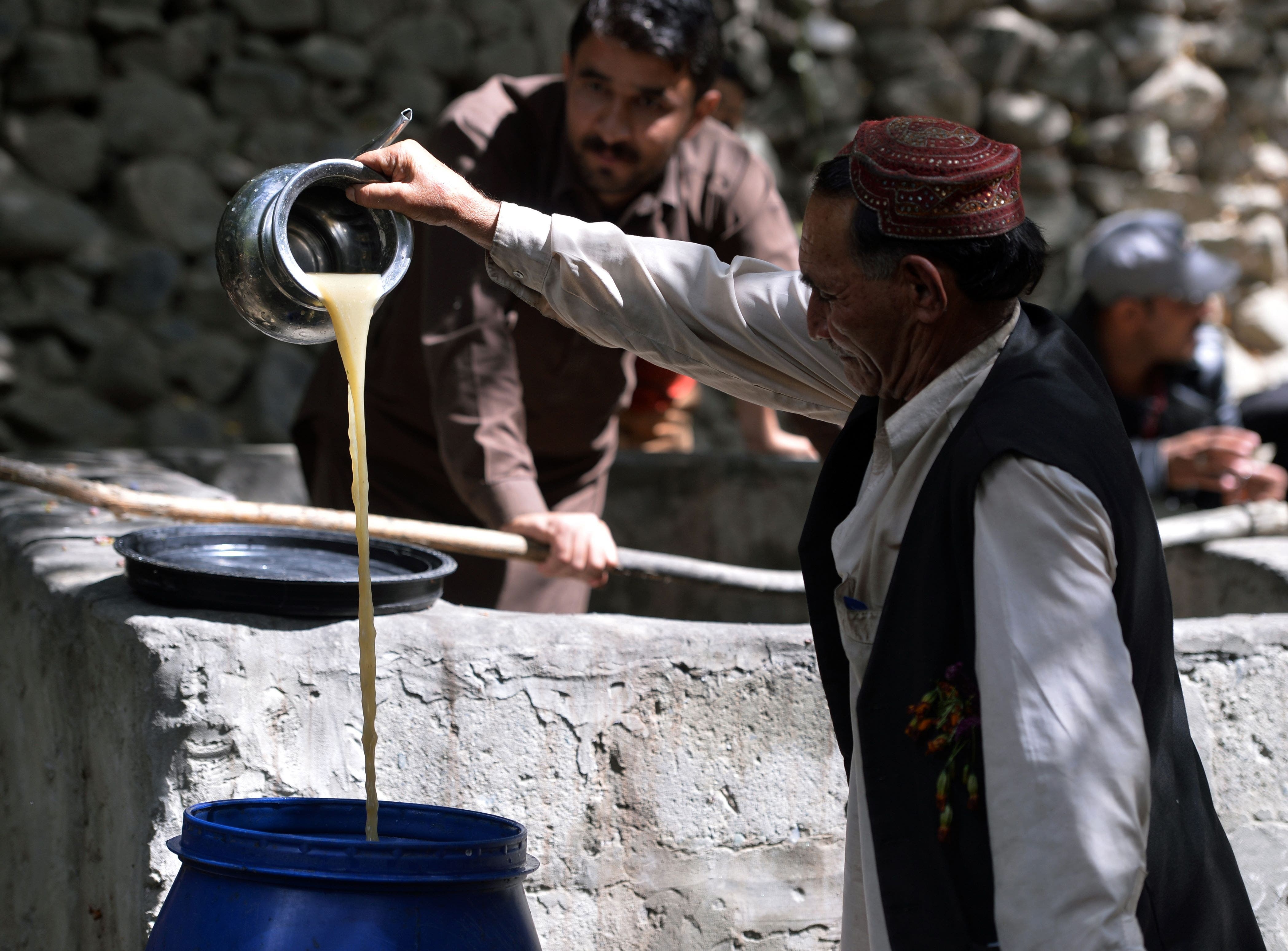 In this photograph taken on September 27, 2015, a local resident pours the juice from crushed grapes as part of a brewing wine process in a garden in the remote village of Sher Qilla in Punyal valley in northern Pakistan.