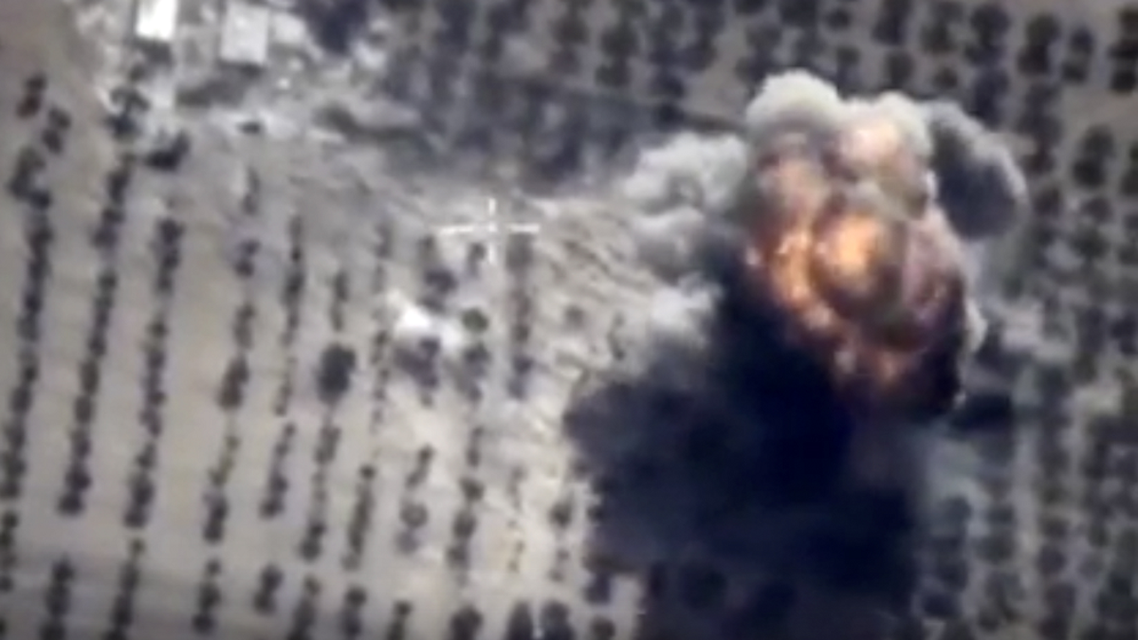 In this photo made from the footage taken from Russian Defense Ministry official web site on Friday, Oct. 16, 2015 showing a target hit during s Russian air raid in Syria. Russian Defense Ministry said the strike was performed by an Su-24M bomber in Idlib province. (AP Photo/ Russian Defense Ministry Press Service)