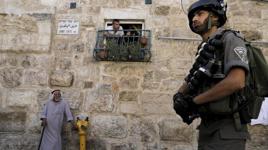 A Palestinian man looks out a window as an Israeli border police officer