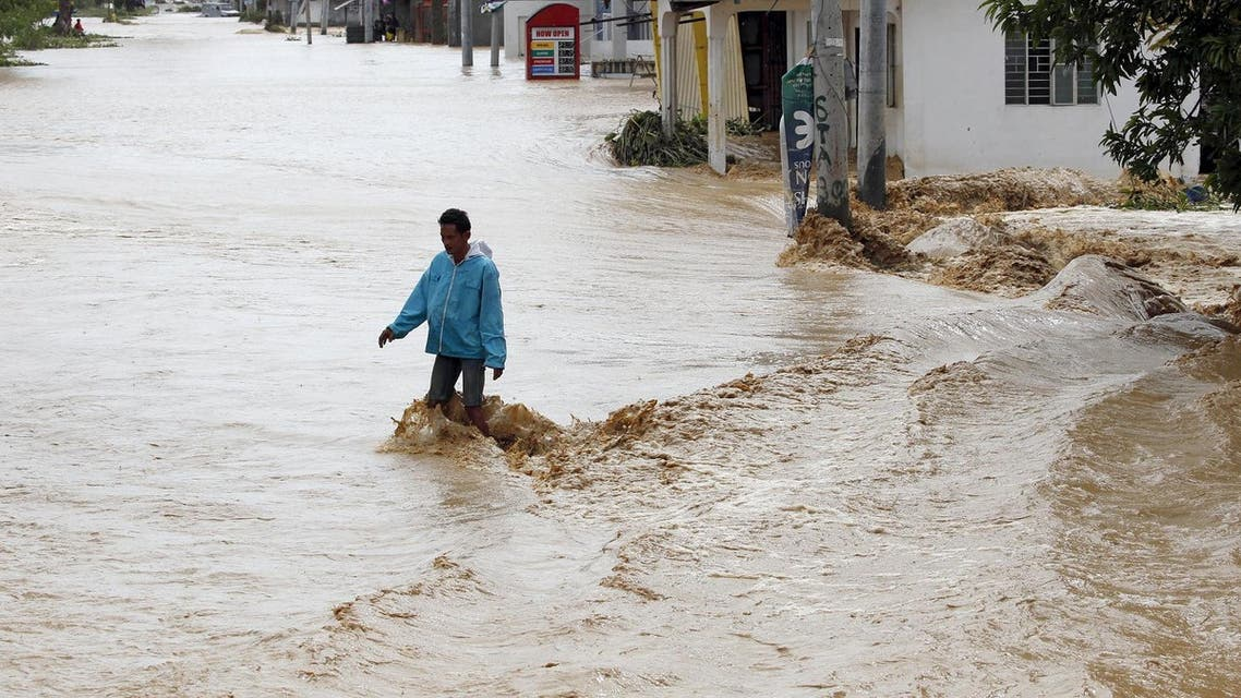 A man tries to cross a road amidst a strong current along a flooded road in Sta Rosa, Nueva Ecija. (Reuters)