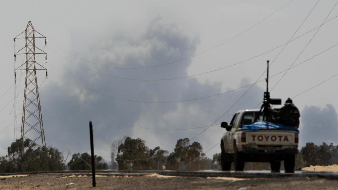 A Libyan rebel vehicle drives toward the town as a large explosion, possibly a NATO airstrike, rises above it in Ajdabiya, Libya Saturday, April 9, 2011. NATO officials did not immediately confirm the attack but the British military said its warplanes hit seven tanks around Ajdabiya and the rebel-held city of Misrata in western Libya on Friday as part of the NATO-led mission. (AP Photo/Ben Curtis)