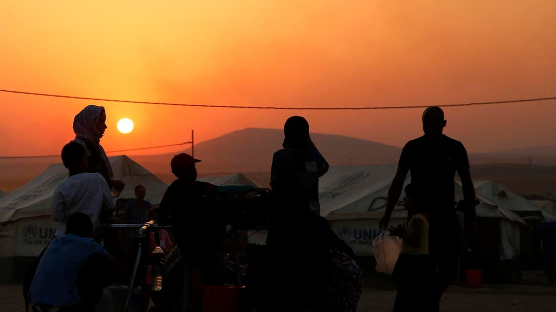 Iraqi refugees, who fled from the violence in Mosul, use containers to collect water during sunset inside the Khazer refugee camp on the outskirts of Arbil, in Iraq's Kurdistan region, June 27, 2014. G