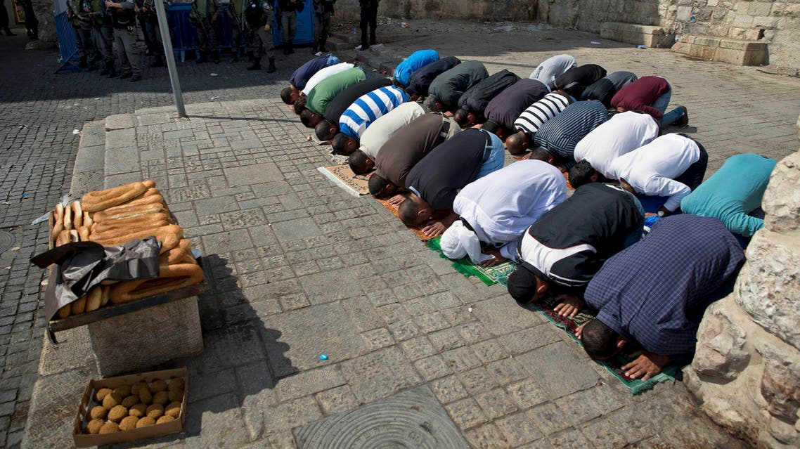Palestinians pray as Israeli border police officers stand guard during Muslim Friday prayers outside the Al-Aqsa Mosque after Israel barred men under 45 from the mosque compound, Friday, Oct. 9, 2015. A rash of individual attacks between Palestinians and Israelis threatened to spread throughout Israel Friday as a 14-year-old Israeli and a police officer were stabbed in separate incidents while an Israeli stabbed four Arabs in the southern city of Dimona. (AP Photo/Ariel Schalit)