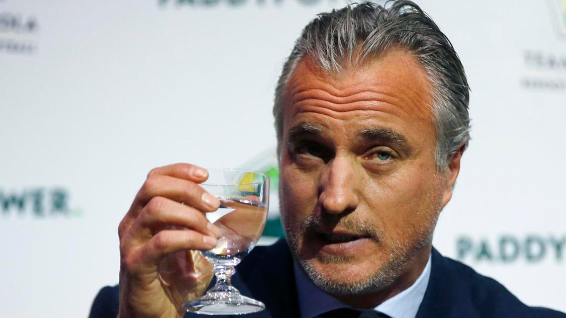 Former France soccer player David Ginola holds up a glass at a press conference to launch his bid to challenge Sepp Blatter for the FIFA presidency, in London, Friday Jan. 16, 2015. (AP)