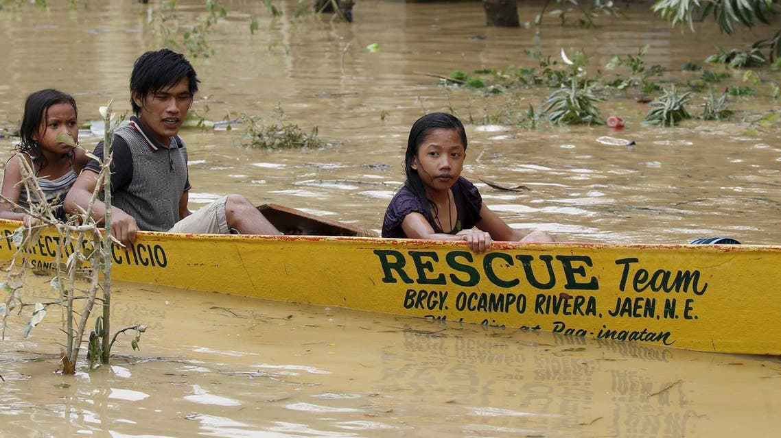 Typhoon victims ride on a rescue boat along a flooded road in Jaen, Nueva Ecija. (Reuters)