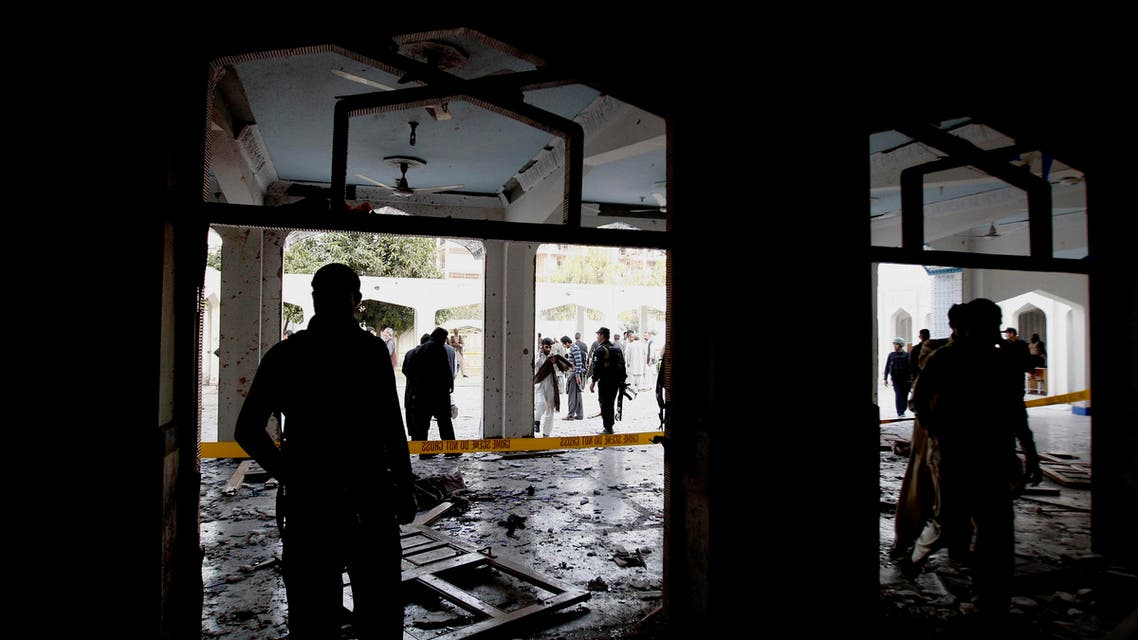 Pakistani security officials look for forensic evidence at a Shiite mosque attacked by militants in Peshawar, Pakistan, Friday, Feb. 13, 2015. AP