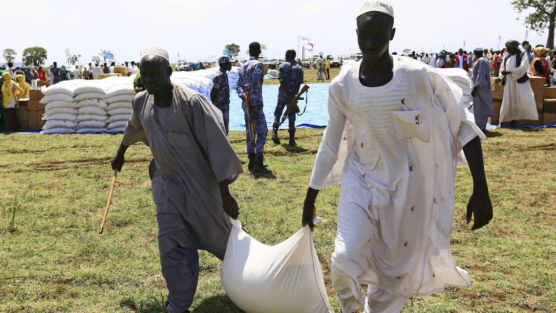 Men carry a sack after receiving food provided by the United Nations' World Food Programme (WFP) during a visit by a European Union delegation, at an Internally Displaced Persons (IDP) camp in Azaza, east of Ad Damazin, capital of Blue Nile state, Sudan October 21, 2015.