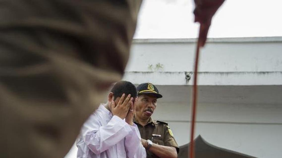 """An Acehnese man convicted for """"immoral acts"""" prepares for punishment to be administered by a hooded local government officer during a public caning at a square in Banda Aceh, Aceh province, on June 12, 2015 ©Chaideer Mahyuddin (AFP)"""