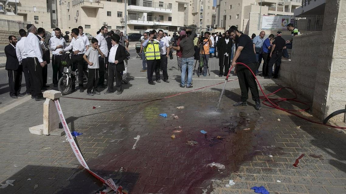 Onlookers stand at the scene of a stabbing, west of Jerusalem, in the town of Beit Shemesh, Israel October 22. (AFP)