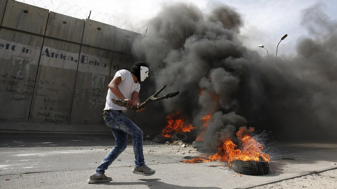 A masked Palestinian protester holds a wooden slingshot as he walks past a section of the Israeli barrier during clashes in the West Bank town of Al-Ram, near Jerusalem October 22, 2015. Nine Israelis have been killed in Palestinian stabbings, shootings and vehicle attacks since the start of October. Forty-nine Palestinians, including 25 assailants, among them children, have been killed in attacks and during anti-Israeli protests. Among the causes of the turmoil is Palestinians' anger at what they see as Jewish encroachment on the al-Aqsa mosque compound in Jerusalem's walled Old City. REUTERS/Mohamad Torokman TPX IMAGES OF THE DAY