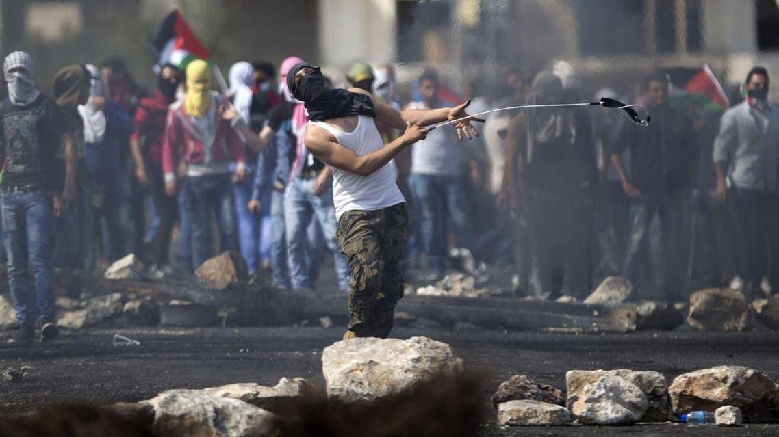 A Palestinian hurls a stone during clashes with Israeli troops, near Ramallah. (AP)